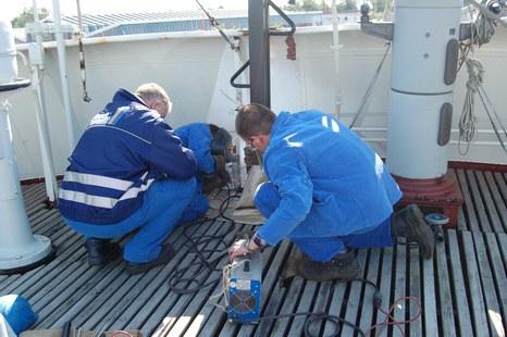 Der Ausbildungsleiter und die Auszubildenden der Lloyd Werft beim Verschweißen des Signalmasts und auf dem Peildeck der 'GERA'
